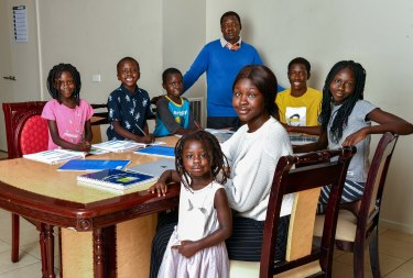 The Dhieu family (front left to right) Nyibol, 3 and  Sobur 20  (back left to right) Adut 5, Athian, 5, Makuei, 7 dad Andrew, 50, Mayen, 17 and Makuei, 7 mostly worked out of one room together during remote learning.