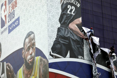 Workers pull down a banner advertising the NBA game between the Brooklyn Nets and the Los Angeles Lakers scheduled for Thursday outside the Super Brand Mall in Shanghai, China.