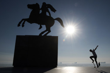 A skateboarder practises next to a bronze statue of Alexander the Great on his famous horse Bucephalus in the northern port city of Thessaloniki , Greece.