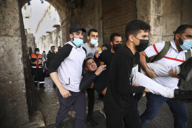 Palestinians evacuate a wounded protester during clashes with Israeli security forces at the Lions Gate in Jerusalem's Old City on May 10.