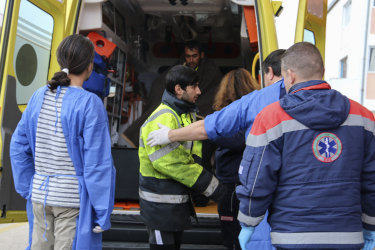 Medical staff transfer a survivor from an ambulance to hospital.