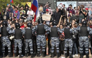 Russian police push protesters back.