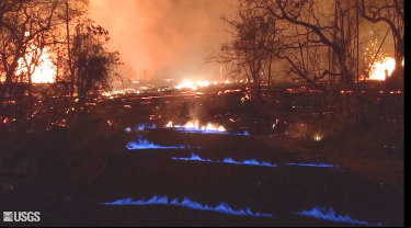 Blue flames of methane gas erupt through cracks on Kahukai Street in the Leilani Estates neighborhood of Pahoa on the island of Hawaii overnight on Wednesday.