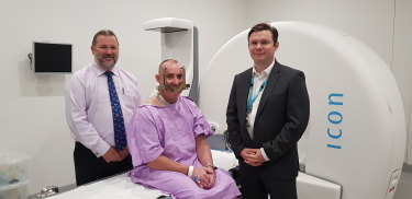 Neurosurgeon Dr Bruce Hall, brain cancer patient Robert Wetherspoon and Radiation Oncologist  Dr Mark Pinkham in front of the Princess Alexandra Hospital's Gamma Knife machine.