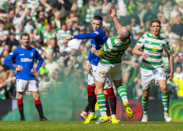 Fiery: Rangers' Ryan Kent clashes with Celtic captain Scott Brown during a combustible Old Firm derby at Parkhead in 2019.