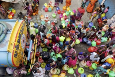 Indians stand in queues to fill vessels filled with drinking water from a water tanker in Chennai, capital of the southern Indian state of Tamil Nadu.