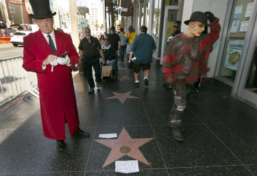 "Gregg Donovan, left, who calls himself the unofficial ambassador of Hollywood, stands next to Bill Cosby's star on the Hollywood Walk Fame, tagged with a ""Guilty on All 3 Counts!"" in Los Angeles on Thursday."