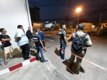 Police and bystanders stand near the scene of a shooting at the Terminal 21 mall, in Korat, Thailand.