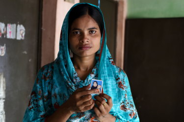 Bangladesh textile worker Tania, 21, holds the only photo of her daughter who lives in a distant village with her grandparents.
