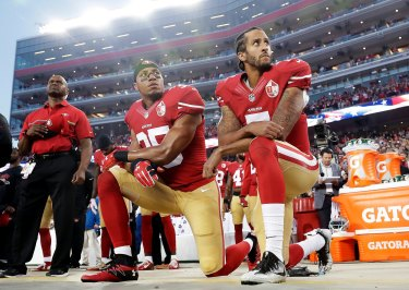 Colin Kaepernick, right, and Eric Reid take a knee during the US national anthem in 2016.
