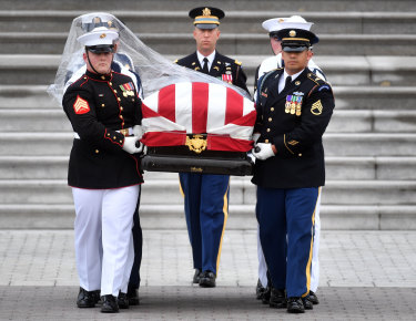 The casket of John McCain is carried down the steps of the US Capitol.