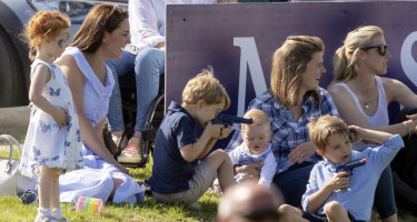 The Duchess of Cambridge, left, sits as Prince George plays with other unidentified spectators at a charity polo event.