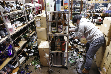 A liquor shop's manager clears the damaged bottles following an earthquake in Fukushima.
