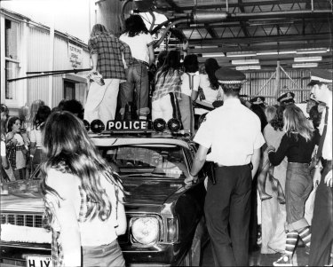 Fans of the Bay City Rollers stand on a police car for a glimpse of their idols. December 4, 1975.