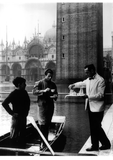 A waiter serves coffee during a flood in Venice.
