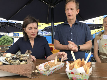 Environment Minister Leeanne Enoch and Eat Street's John Harrison inspect cups made from corn starch and biodegradable utensils.