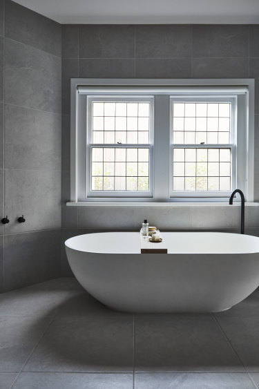"""A former study was transformed into a spacious bathroom as part of the main bedroom suite. The stone """"Moda"""" bath is from ACS Designer Bathrooms."""