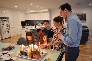 "Joshua, his wife Kirsten and their three children chant blessings just after lighting six candles to signify the ""sixth"" day of Hanukkah."