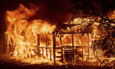 A home is engulfed in flames as fire rages through the Carr region.