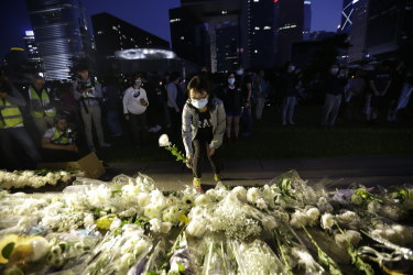 A woman places a flower at a vigil for student Chow Tsz-Lok in Hong Kong on Saturday