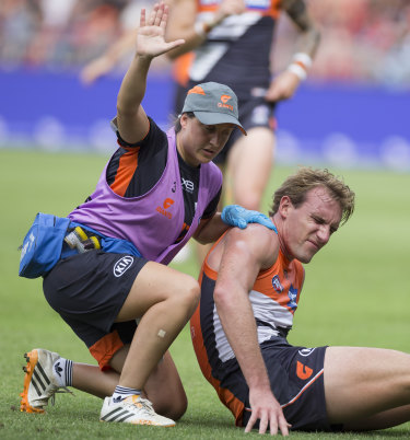 Trouble: A trainer calls for attention after Lachie Keeffe's awkward fall against Essendon.