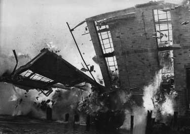 A wall collapses into Blackwattle Bay during the $4 million fire which destroyed the John Fairfax and Sons Limited paper store yesterday. February 9, 1971.