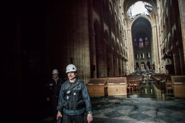 A man walks inside the damaged Notre Dame cathedral on Tuesday.