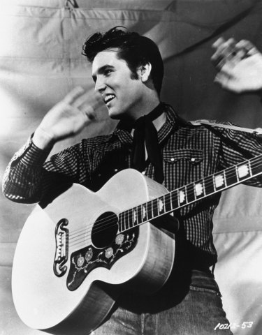 Rock 'n' roll legend Elvis Presley with his Gibson guitar.
