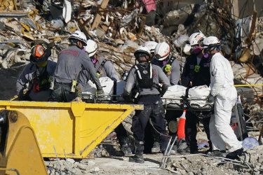 Search and rescue personnel remove remains on a stretcher.