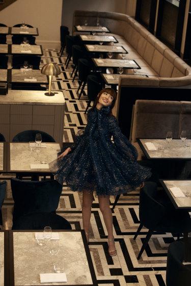 "Bela wears Zimmermann ""Rhythm ruched glitter"" dress, $1850, and Essen shoes, $329."