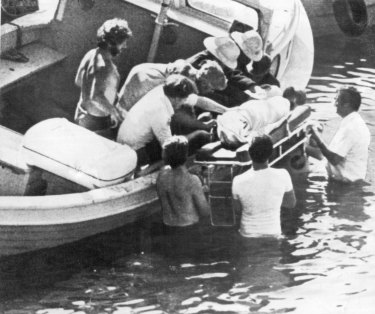 """Rescue workers lift an unidentified body from a small boat in Mullaghmore harbour Monday, after an explosion aboard a fishing boat Killed Earl Mountbatten of Burma, and two other people."""