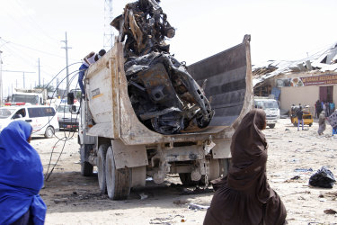 A truck carries wreckage of a car used in a bomb.