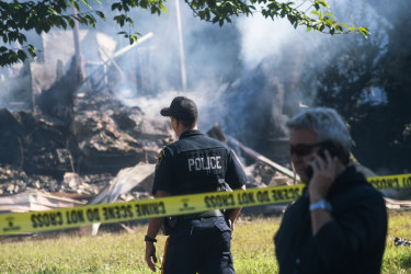 Police stand guard near the remains of a house that exploded due to severe flooding.