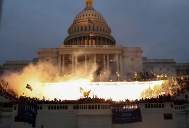 An explosion caused by a police munition is seen while supporters of US President Donald Trump storm the Capitol building.