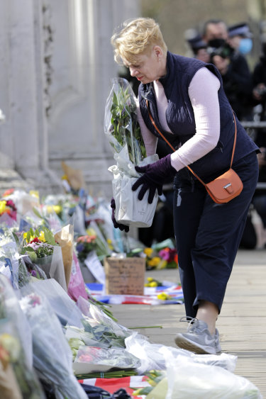 A member of the public leaves a floral tribute.