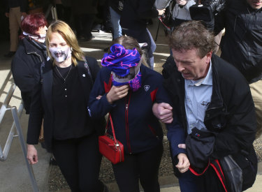The 19-year old British woman covers her face as she leaves from the court.