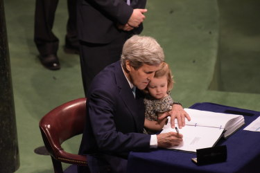 John Kerry signing the Paris Accords to reduce global greenhouse emissions to tackle climate change in 2016 with his granddaughter.  As President Biden's special climate envoy, Kerry is expected to lead America's diplomatic efforts to accelerate climate action globally.