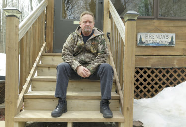 Shocked: Neighbour Wayne Sankey sits on the front steps of his Lakewood home.