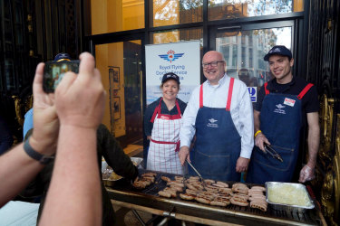 Australia's High Commissioner to the UK George Brandis serves democracy sausages to voters at Australia House in London.