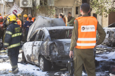 Security force personnel look at a burned car after a rocket fired from Gaza Strip hit on Saturday.
