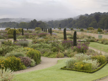 Mist rises from the lake in the distance beyond this garden in Staffordshire, Britain.
