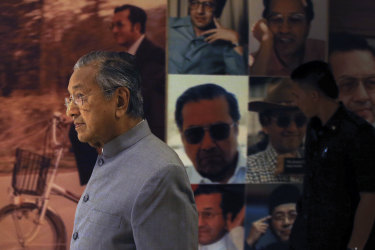 Malaysian Prime Minister Mahathir Mohamad walks by a board displaying his photos in Putrajaya, Malaysia.