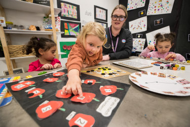 Goodstart Flinders Street director Chelsea Snowden plays a counting game with children Angelique, Mila and Lara.