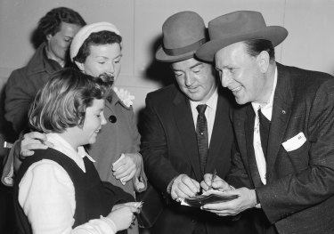 US actors and comedians Bud Abbott (right) and Lou Costello meet some fans upon their arrival at Sydney's Mascot Airport on 15 June 1955 for a series of shows.