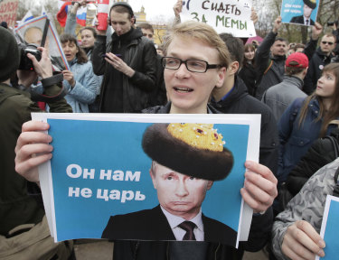 Demonstrators carry posters depicting Russian President Vladimir Putin during a massive protest rally in St.Petersburg.