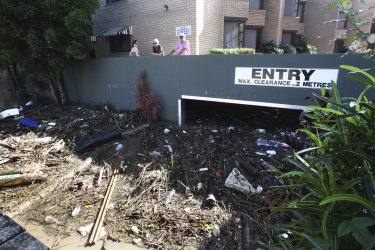 Ross and Ronnie Girdham look at the garbage and debris surrounding their riverside units in Toowong.
