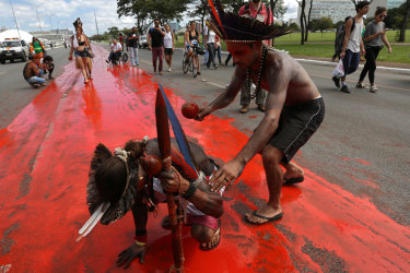 Brazilian indigenous people paint a road to depict the blood of those killed in the struggle for their lands.