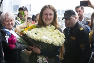 Maria Butina holds a bunch of flowers as she lands in Russia.