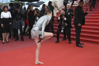 Kristen Stewart removes her shoes at the premiere of the film 'BlacKkKlansman' at the 71st Cannes Film Festival.