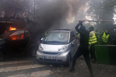 Hooded demonstrators smash a car during a demonstration.